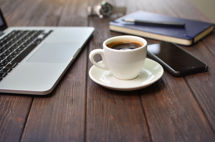 A coffee cup with a laptop and other work supplies on a table