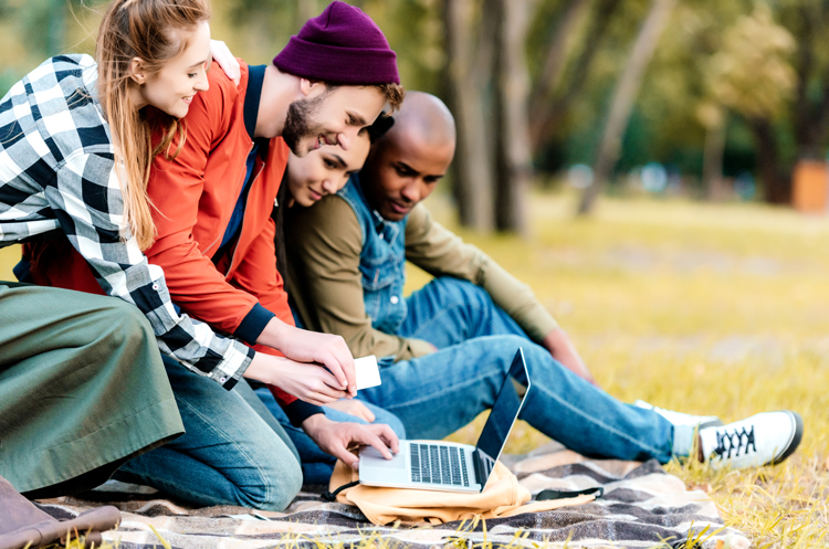 A group of young people in the park looking at a laptop