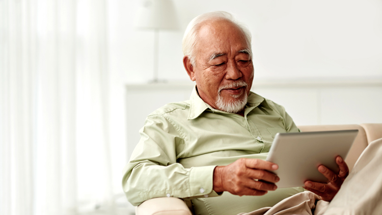 Elderly Man Sitting on Couch Looking at Tablet