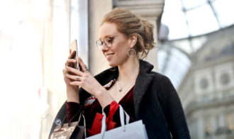 Woman with shopping bags looking at smartphone