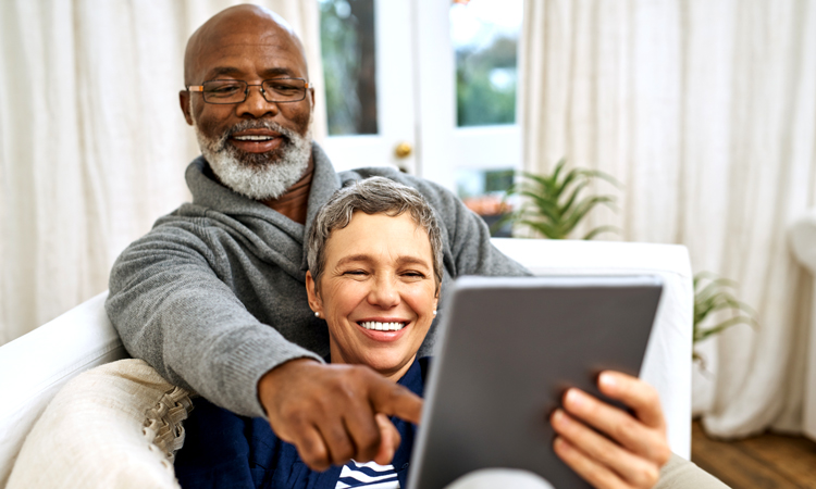 Man and woman pointing at a tablet
