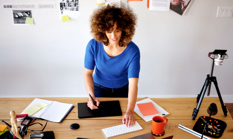 Woman stands at desk
